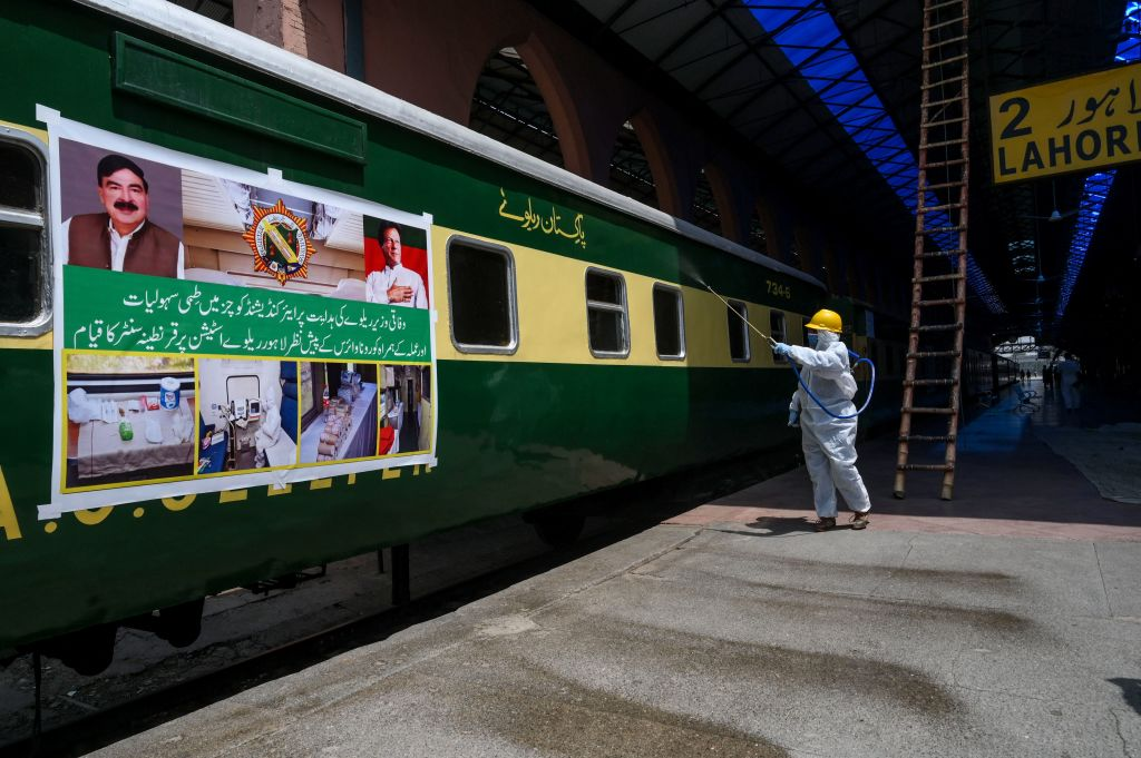 A worker wearing protective gear sprays disinfectant on a train at the Lahore railway station during a government-imposed nationwide lockdown as a preventive measure against the COVID-19 coronavirus, in Lahore on May 7, 2020. (Photo by ARIF ALI/AFP via Getty Images)