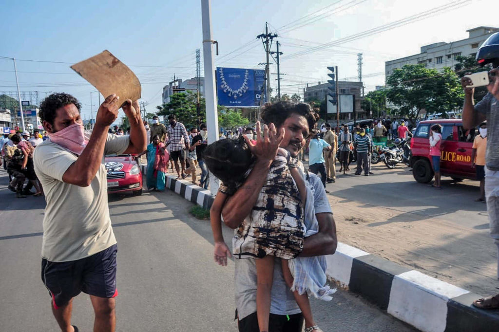 FILE PHOTO: A man carries a fainted young girl (R) to evacuate her following a gas leak incident at an LG Polymers plant in Visakhapatnam on May 7, 2020. - Eleven people were killed and hundreds hospitalised after a pre-dawn gas leak at a chemical plant in eastern India on May 7 that left unconscious victims lying in the streets, authorities said. (Photo by STR/AFP via Getty Images)