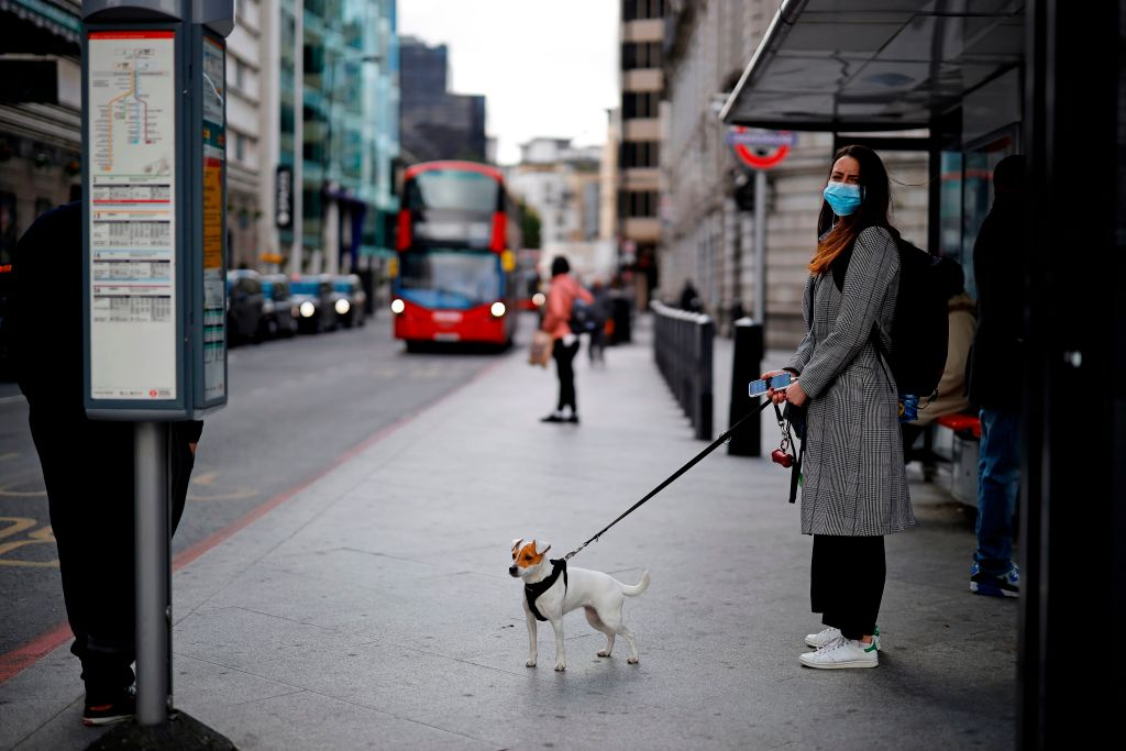 A commuter wearing  a face mask as a precautionary measure against Covid-19, waits to catch a bus in the morning rush hour on May 11, 2020, in London. (Photo: TOLGA AKMEN/AFP via Getty Images)