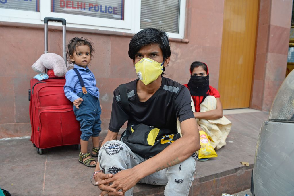 Rajan (C) and his wife along with their 15-month-old son Yash Kumar, who is suffering from heart disease, wait outside a railway station in New Delhi on May 12, 2020. - Rajan and his family got stranded in the capital where he brought his son for treatment from Bihar after the government imposed a nationwide lockdown to fight against the spread of the COVID-19 coronavirus. (Photo by SAJJAD HUSSAIN/AFP via Getty Images)