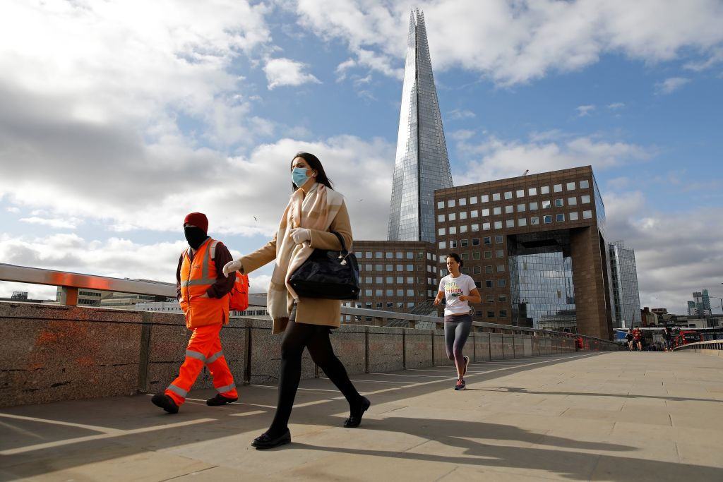 Commuters wearing PPE including a face mask, walk across the London Bridge towards the City, near The Shard, in central London on May 13, 2020, as people start to return to work after Covid-19 lockdown restrictions were eased. (Photo: TOLGA AKMEN/AFP via Getty Images)