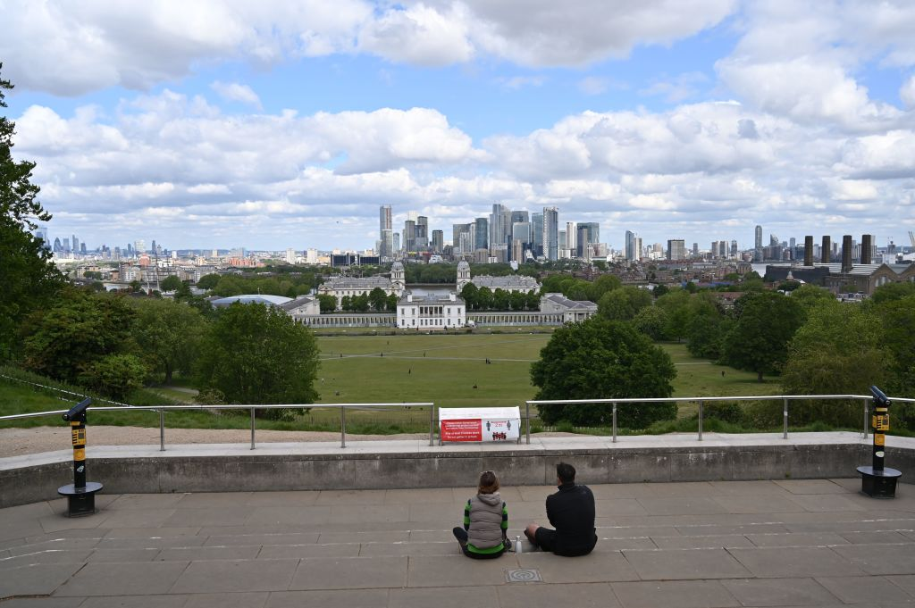 A couple sit on the viewing platform with Greenwich Park and the office buildings of the financial district of Canary Wharf in the background in London on May 14, 2020. (Photo: GLYN KIRK/AFP via Getty Images)