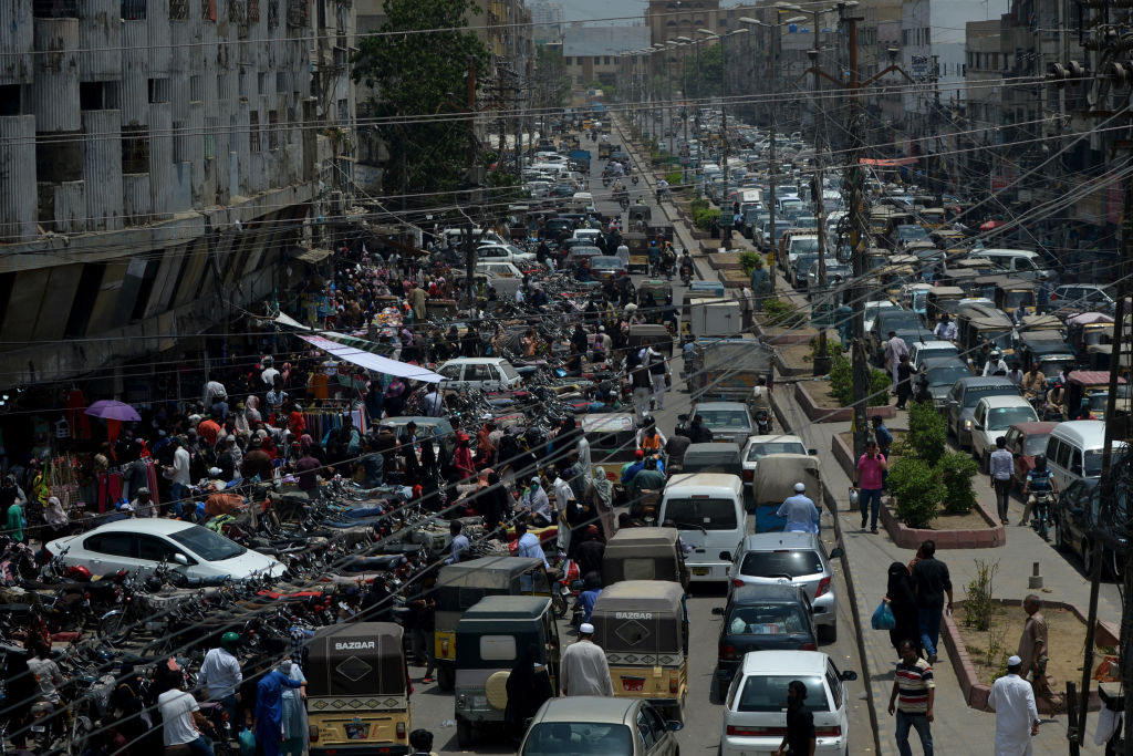 Commuters make their way along a busy street in a market area after the government eased the nationwide lockdown imposed as a preventive measure against the COVID-19 coronavirus, in Karachi. (Photo by RIZWAN TABASSUM/AFP via Getty Images)
