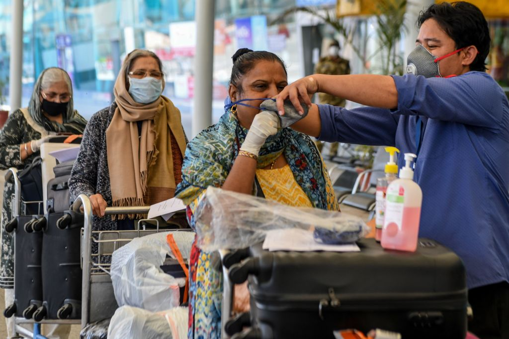 A British High Commission worker (R) distributes facemasks to passengers queuing before checking-in for a special flight to London at Sri Guru Ram Dass Jee International Airport on the outskirts of Amritsar on May 15, 2020. (Photo: NARINDER NANU/AFP via Getty Images)