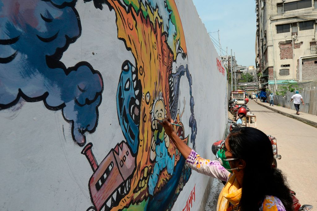 A female activist paints a graffiti depicting the COVID-19 coronavirus during a government-imposed lockdown as a preventive measure against the COVID-19 coronavirus, in Narayanganj on May 18, 2020. (Photo by MUNIR UZ ZAMAN/AFP via Getty Images)