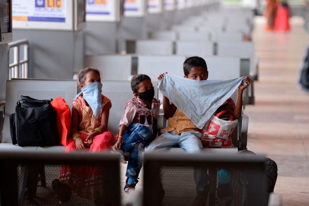 Children with their face covered wait to board on a bus as Telangana State Road Transport Corporation (TSRTC) resumed bus services after the government eased a nationwide lockdown imposed as a preventive measure against the COVID-19 coronavirus, at Jubilee Bus Station (JBS) in Secunderabad, the twin city of Hyderabad on May 19, 2020. (Photo by NOAH SEELAM/AFP via Getty Images)