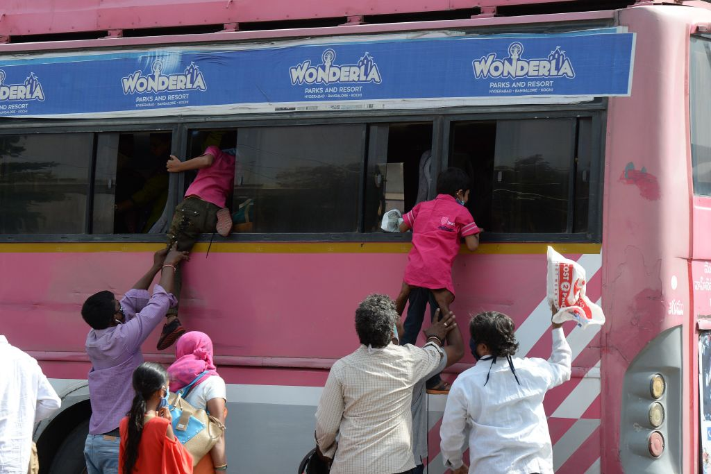 Passengers board children through the window of a bus as Telangana State Road Transport Corporation (TSRTC) resumed bus services after the government eased a nationwide lockdown imposed as a preventive measure against the COVID-19 coronavirus, at Jubilee Bus Station (JBS) in Secunderabad, the twin city of Hyderabad on May 20, 2020. (Photo by NOAH SEELAM/AFP via Getty Images)