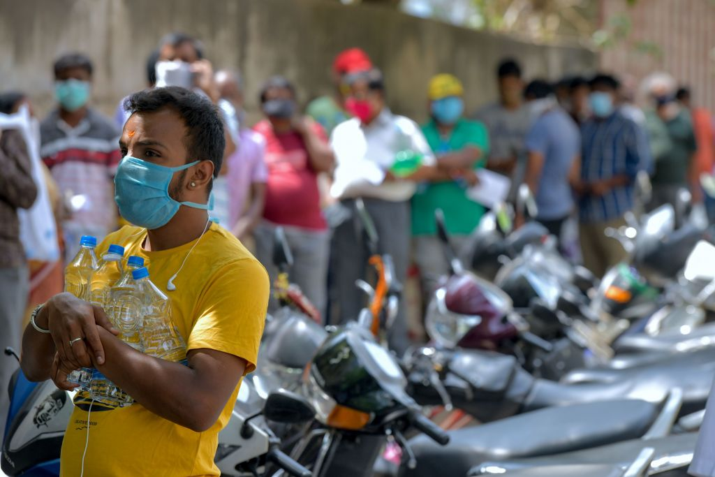 A man carries bottles of water as he queues up with other people in front of a private hospital to get alternative medicine derived from Ayurveda, homeopathy and naturopathy that claim to boost immunity, as a preventive measure against the COVID-19 coronavirus, in Bangalore on May 20, 2020. (Photo by MANJUNATH KIRAN/AFP via Getty Images)