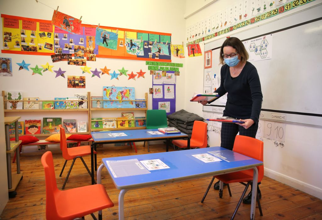 Head teacher Charlotte Beyazian places plastic bags containing materials on the tables for each pupil to help provide a teaching environment safe from coronavirus for pupils and teachers at La Petite Ecole Bilingue at Kentish Town, north London.(Photo: ISABEL INFANTES/AFP via Getty Images)