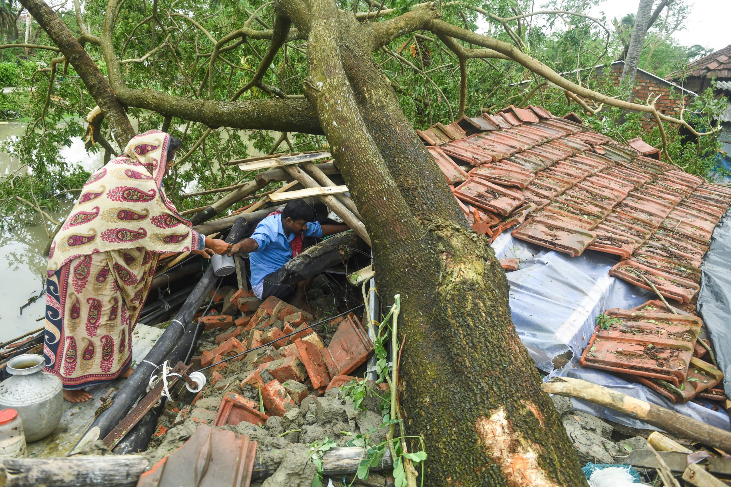 Villagers salvage items from their house damaged by cyclone Amphan in Midnapore, West Bengal, on May 21, 2020. - The strongest cyclone in decades slammed into Bangladesh and eastern India on May 20, sending water surging inland and leaving a trail of destruction as the death toll rose to at least nine. (Photo by Dibyangshu SARKAR / AFP) (Photo by DIBYANGSHU SARKAR/AFP via Getty Images)
