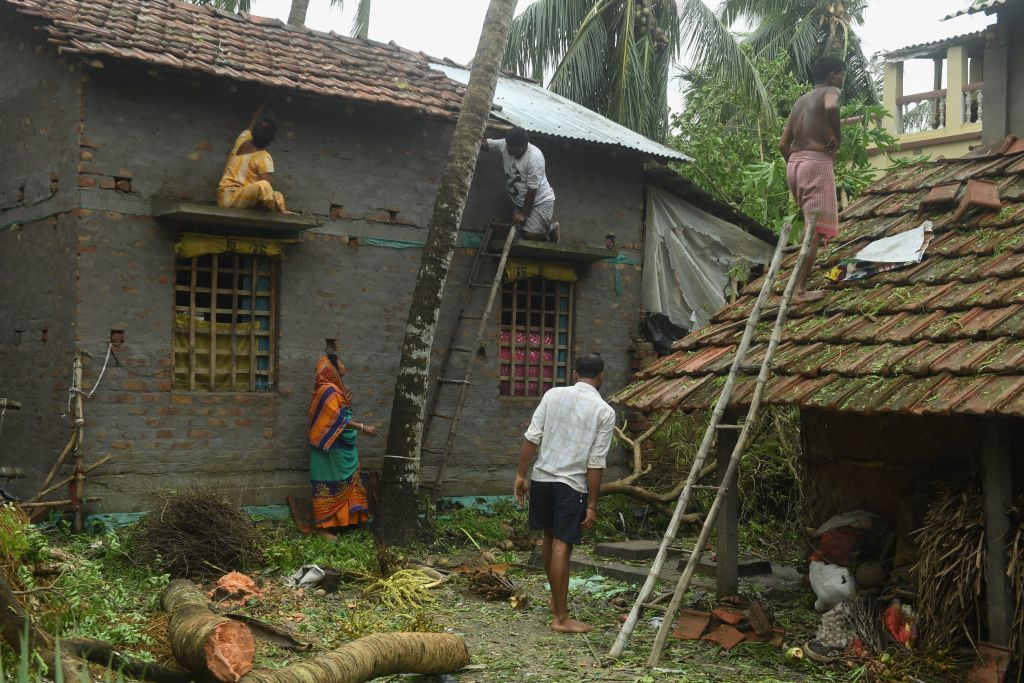 Residents repair the damaged roof of their houses following the landfall of cyclone Amphan in Khejuri area of Midnapore, West Bengal. (Photo by DIBYANGSHU SARKAR/AFP via Getty Images)
