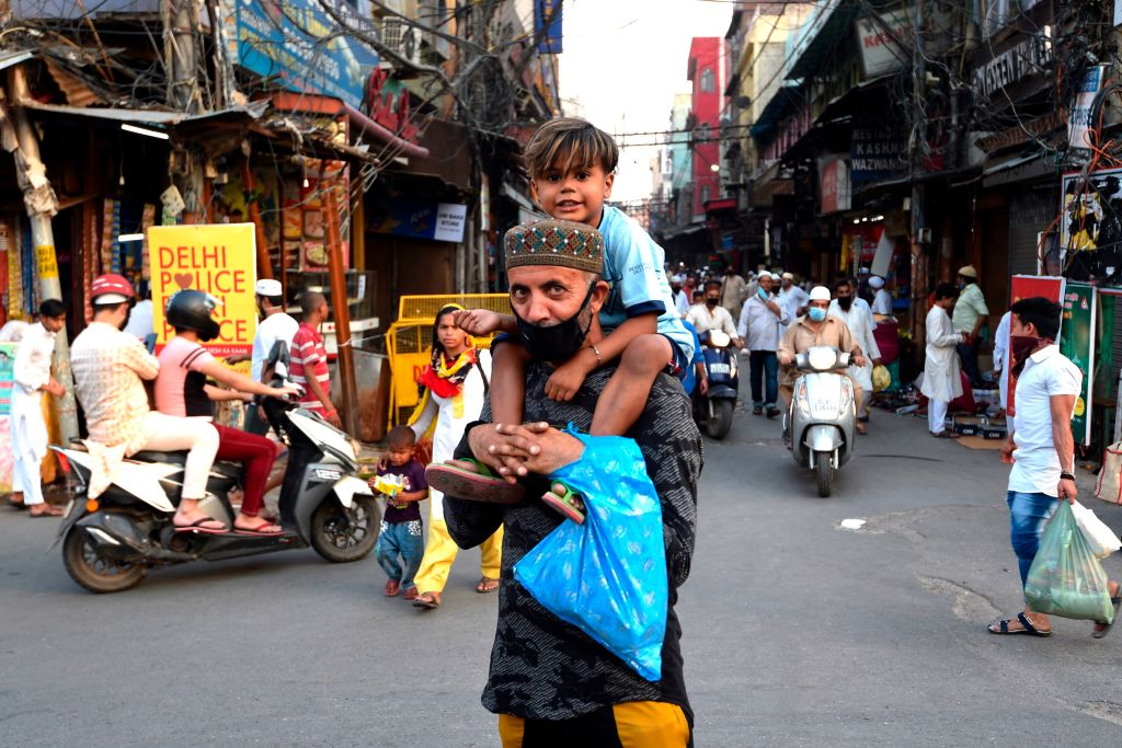 A man carries his son on his shoulders on the last Friday of Ramadan after the government eased restrictions imposed as a preventive measure against the spread of the COVID-19 Coronavirus in the old quarters of New Delhi on May 22, 2020. (Photo by MONEY SHARMA/AFP via Getty Images)