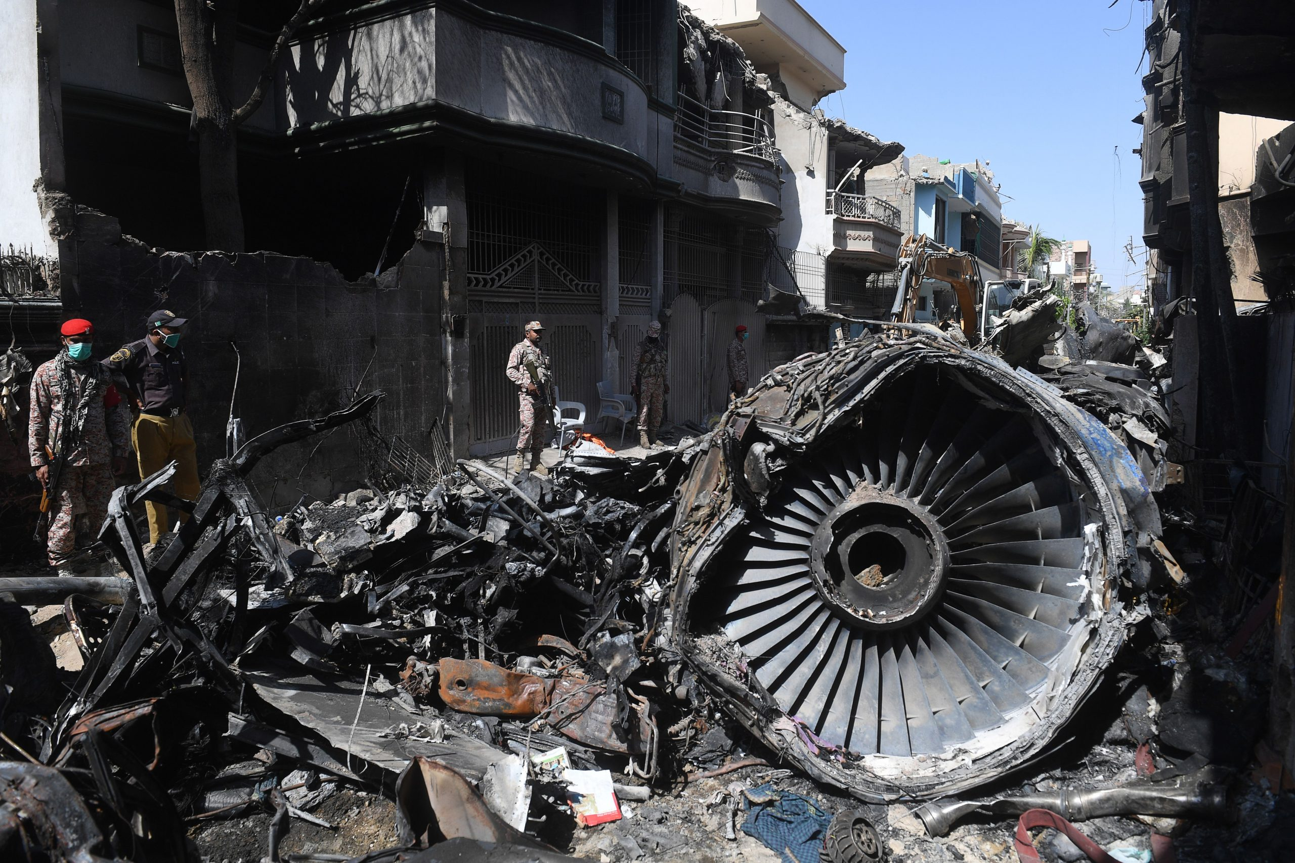 FILE PHOTO: Security personnel stand beside the wreckage of a plane at the site after a Pakistan International Airlines aircraft crashed in a residential area days before, in Karachi on May 24, 2020. (Photo by ASIF HASSAN/AFP via Getty Images)