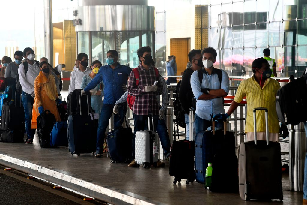 Passengers queue at the airport to board a flight during the first day of resuming of domestic flights after the government imposed a nationwide lockdown as a preventive measure against the spread of the COVID-19 coronavirus, in Mumbai on May 25, 2020. (Photo by INDRANIL MUKHERJEE/AFP via Getty Images)