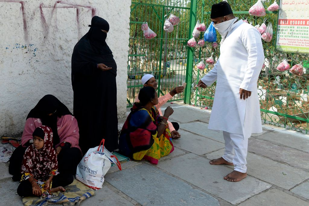 A Muslim devotee (R) gives alms to beggars at the entrance of a graveyard after offering prayers during Eid al-Fitr festival, which marks the end of Islamic holy fasting month of Ramadan, in Secunderabad, the twin city of Hyderabad on May 25, 2020. (Photo by NOAH SEELAM/AFP via Getty Images)