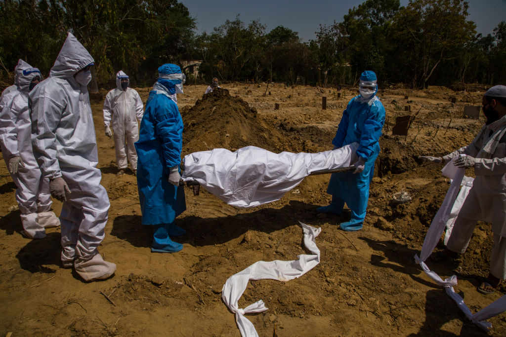Indian health workers in hazmat suits bury a 55-year-old Muslim who died from the coronavirus (COVID-19), during Eid ul-Fitr, the Muslim festival marking the end of the holy fasting month of Ramadan, on May 25, 2020 in Delhi, India. (Photo by Yawar Nazir/Getty Images)
