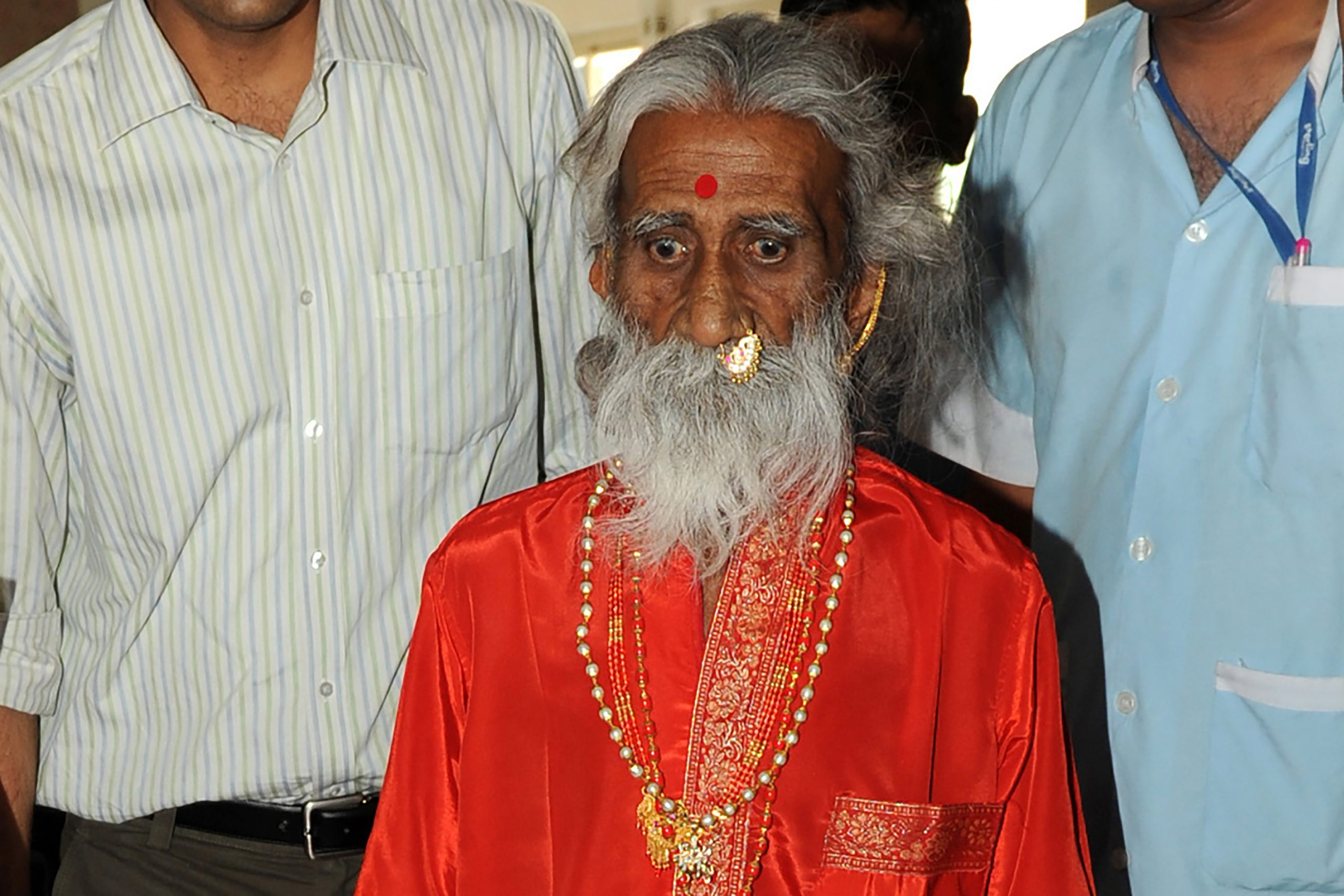 Indian sadhu (Hindu holy man) Prahlad Jani is escorted by devotees and relatives after a press conference in Ahmedbad on May 6, 2010.  A team of military doctors backed by India's national defence research centre is studying an 83-year-old holy man who claims to have spent seven decades surviving without food or water. AFP PHOTO/ Sam PANTHAKY (Photo by SAM PANTHAKY / AFP) (Photo by SAM PANTHAKY/AFP via Getty Images)