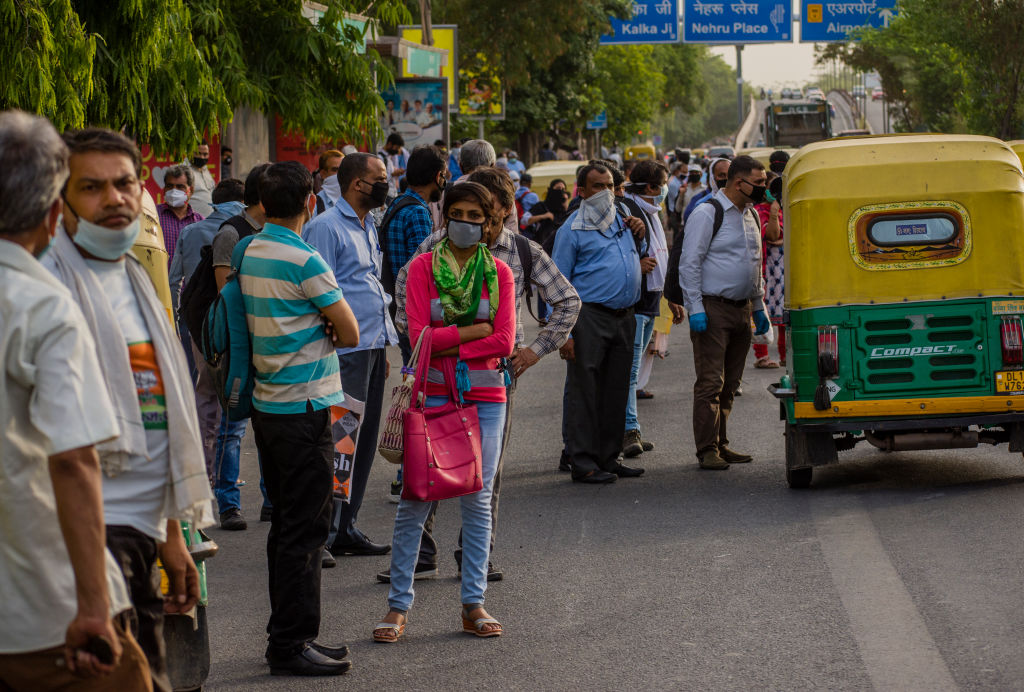 Commuters wait for vehicles, as the country relaxed its lockdown restriction on May 26, 2020 in Delhi, India. (Photo by Yawar Nazir/Getty Images)