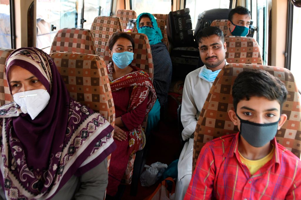 Pakistani nationals, who were stranded in India following the closure of borders due to the COVID-19 coronavirus lockdown, sit inside a mini bus before crossing the India-Pakistan Wagah border post, some 35 kms from Amritsar on May 27, 2020. (Photo by NARINDER NANU/AFP via Getty Images)