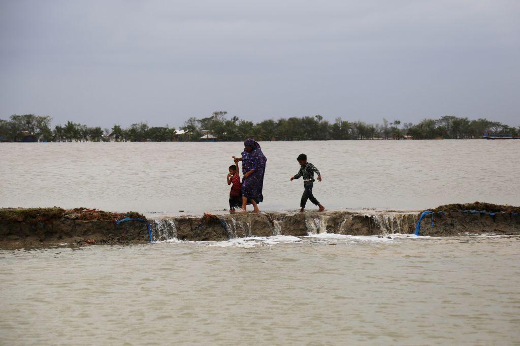 A woman with her children makes her way through a dam damaged by cyclone Amphan inKoyra, Satkhira, on May 27, 2020. (Photo by KAZI SANTO/AFP via Getty Images)