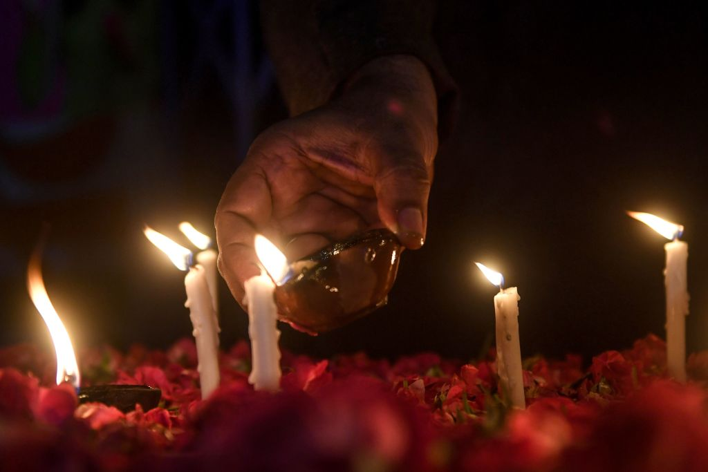 A member of the Majlis Wahdat-e-Muslimeen, a Pakistani Shiite political organization, lights candles in Karachi on May 27, 2020, during a vigil for the victims of the Pakistan International Airlines (PIA) plane crash on May 22. (Photo by ASIF HASSAN/AFP via Getty Images)