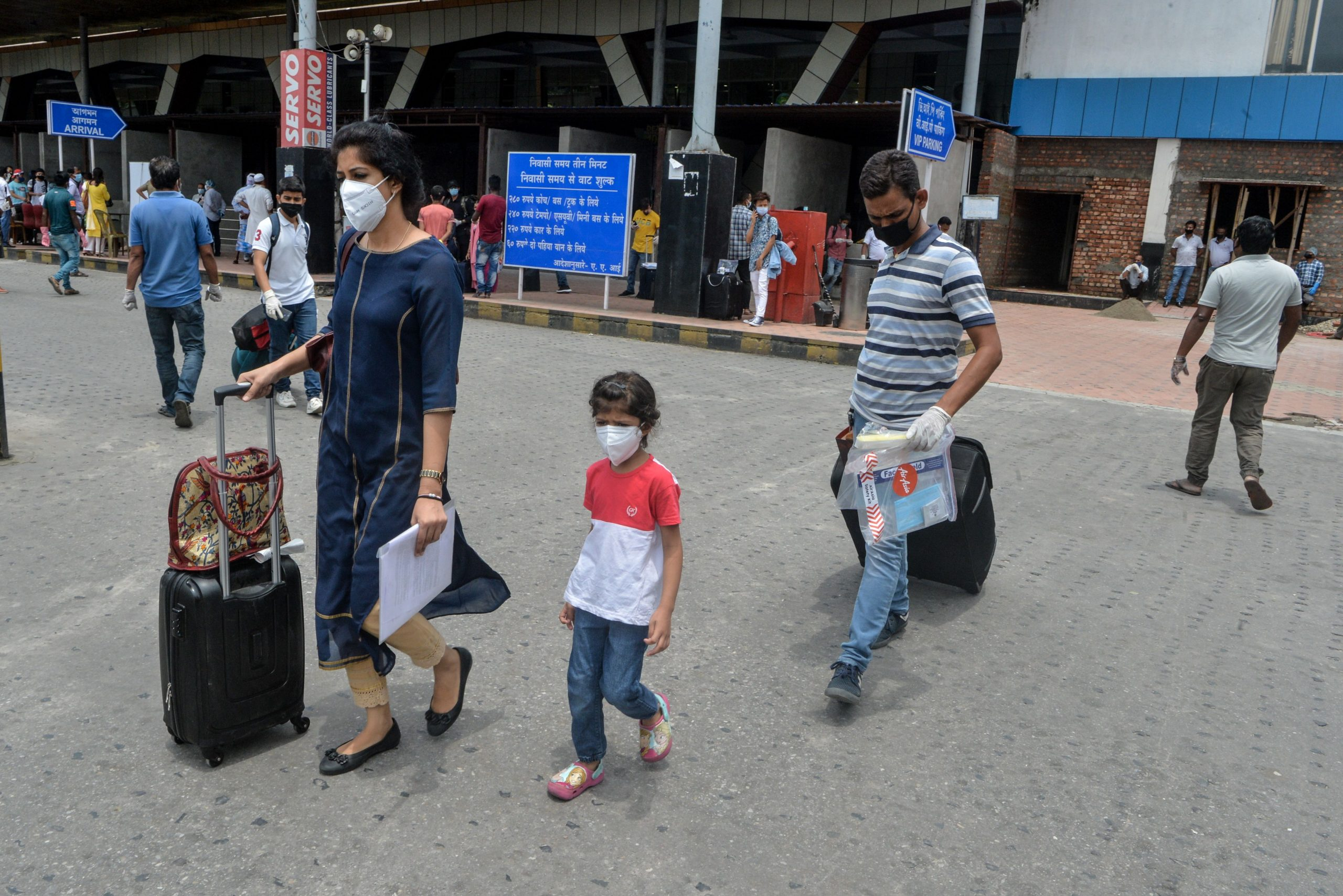 Arriving passengers wearing facemasks leave carrying their luggage at Bagdogra airport after the goverment eased a nationwide lockdown imposed as a preventive measure against the COVID-19 coronavirus, on the outskirts of Siliguri on May 28, 2020. - Domestic air travel will resume in India on May 25 and in West Bengal on May 28 after a two-month shutdown over the coronavirus pandemic. (Photo by DIPTENDU DUTTA / AFP) (Photo by DIPTENDU DUTTA/AFP via Getty Images)