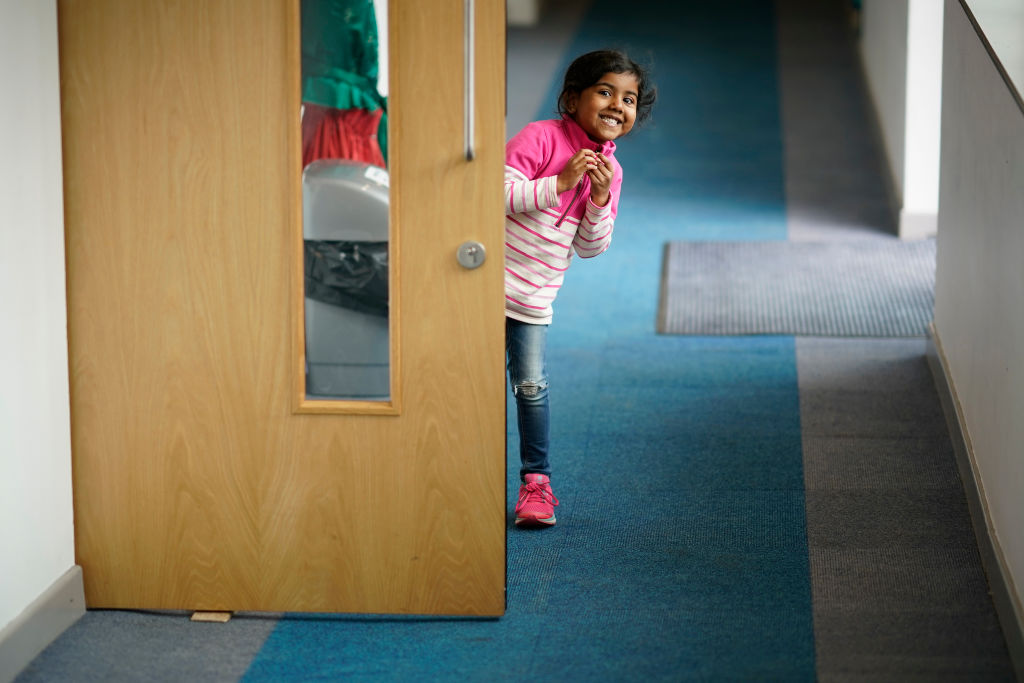 File photo: A young girl peeps around the classroom door at the photographer as children of key workers take part in school activities at Oldfield Brow Primary School in Altrincham, England. (Photo: Christopher Furlong/Getty Images)