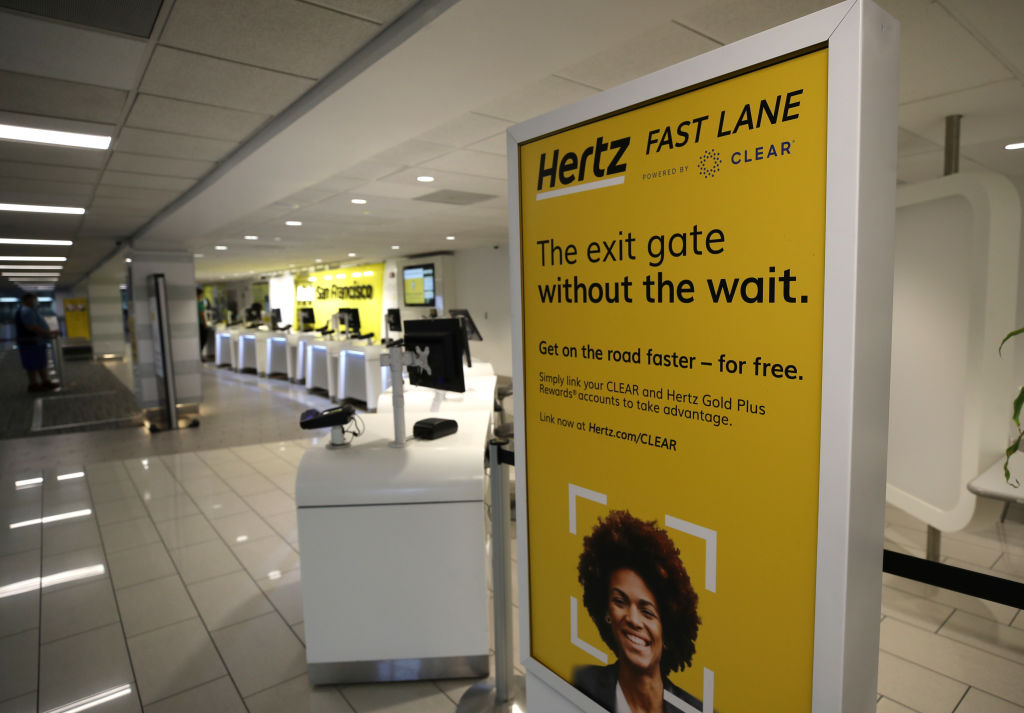 A sign is posted in the entrance to the Hertz Rent-A-Car desk at San Francisco International Airport in San Francisco, California. (Photo by Justin Sullivan/Getty Images)