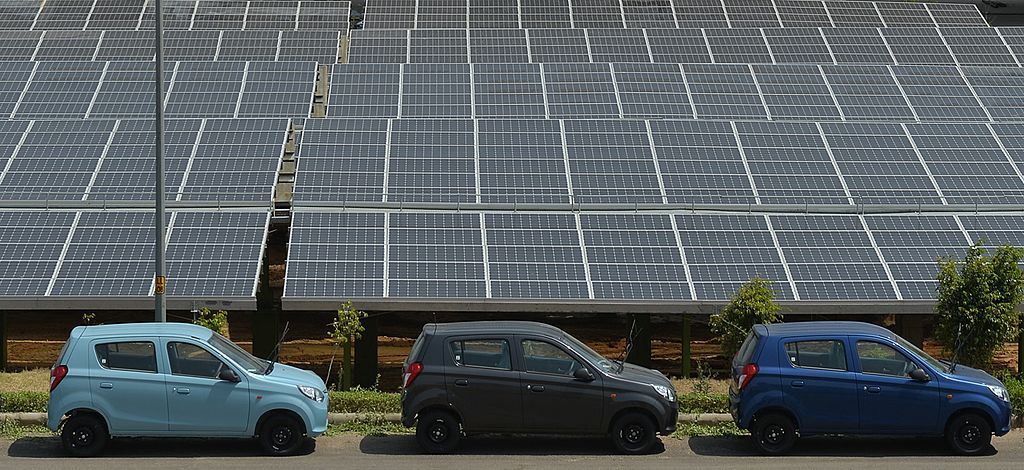 FILE PHOTO: Newly finished cars stand next to solar panels at a solar power plant built on the site of Indian vehicle manufacturer Maruti Suzuki at Manesar on the outskirts of New Delhi (Chandan Khanna/AFP via Getty Images)