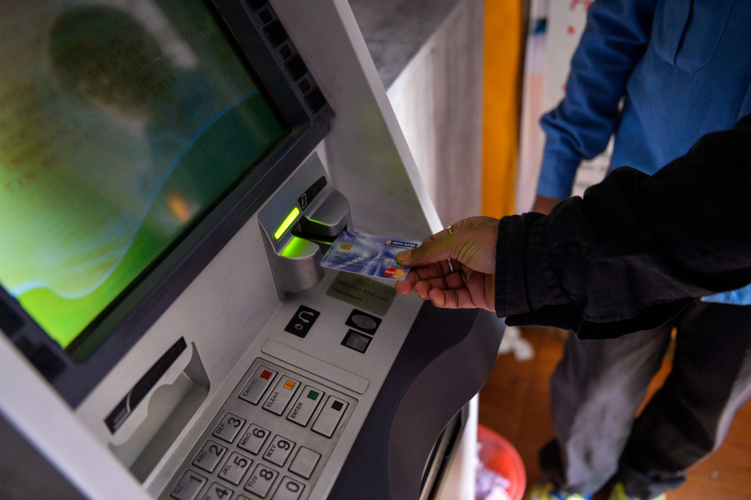 """An Indian man inserts his card to withdraw money from a mobile bank ATM machine in New Delhi on November 15, 2016. India is to use indelible ink to prevent people from exchanging old notes more than once, the government said, a week after the withdrawal of high-value banknotes from circulation in a crackdown on """"black money"""". / AFP PHOTO / CHANDAN KHANNA        (Photo credit should read CHANDAN KHANNA/AFP via Getty Images)"""