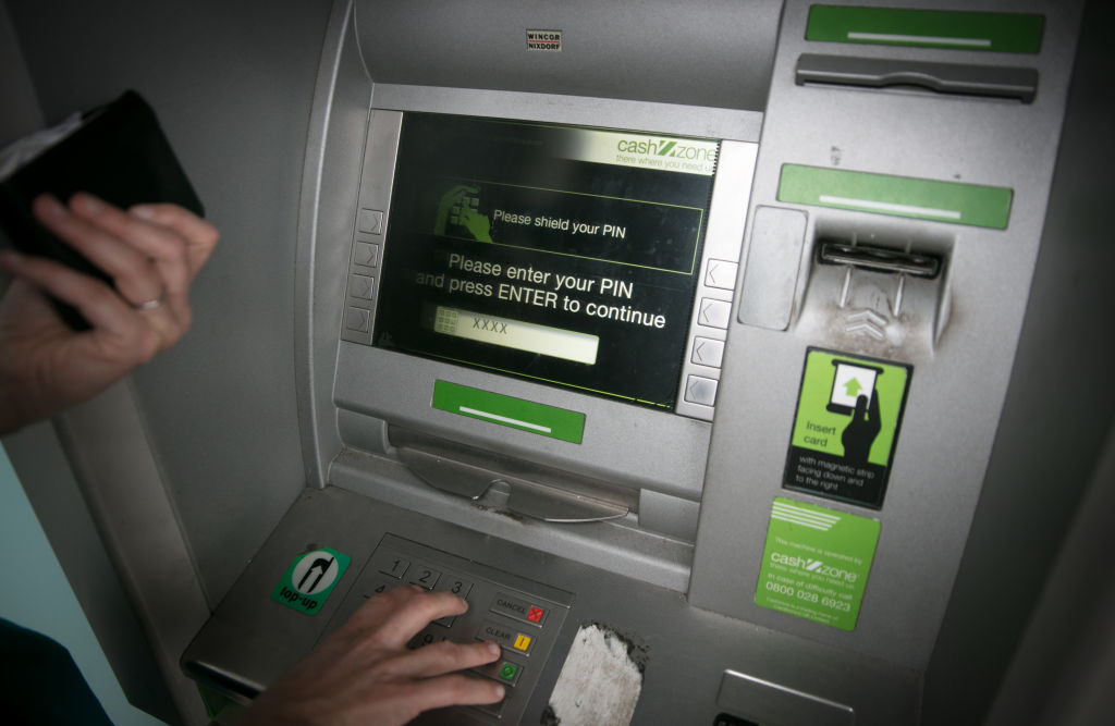 FILE PHOTO: A woman uses a cashpoint ATM in Bristol, England.  (Photo by Matt Cardy/Getty Images)