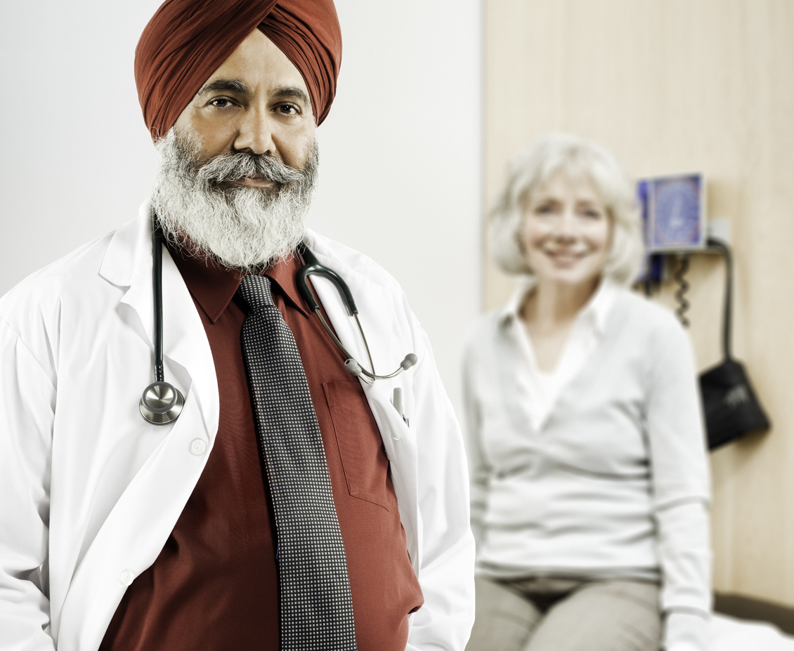 Doctor in a lab coat and turban poses for the camera while his patient sits in the background on an examination table.