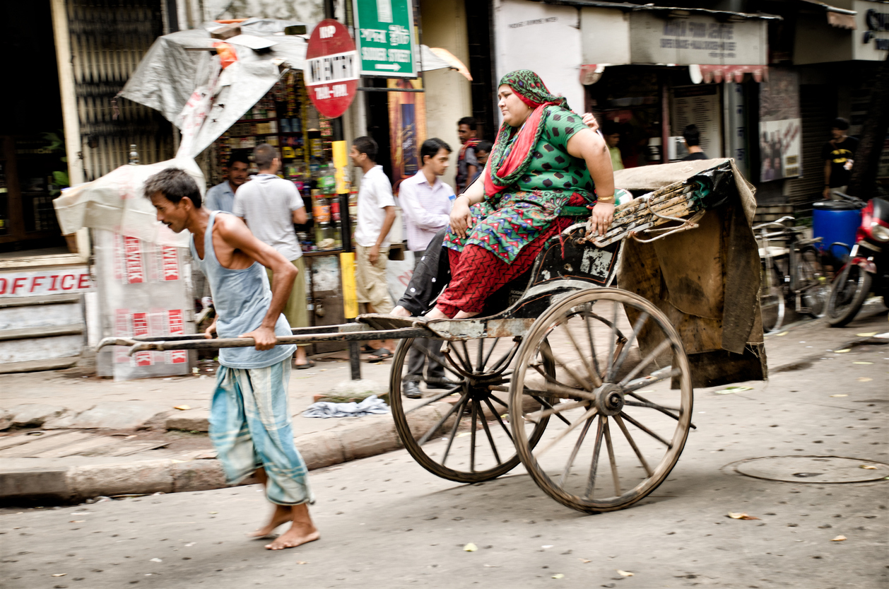 Kolkata, India - August 19, 2012: Unidentified man pulls a fat woman on his rikshaw.  In 2006, the chief minister of West Bengal announced that pulled rickshaws would be banned and that rickshaw pullers would be rehabilitated, but actually they're still working in the street of Kolkata.
