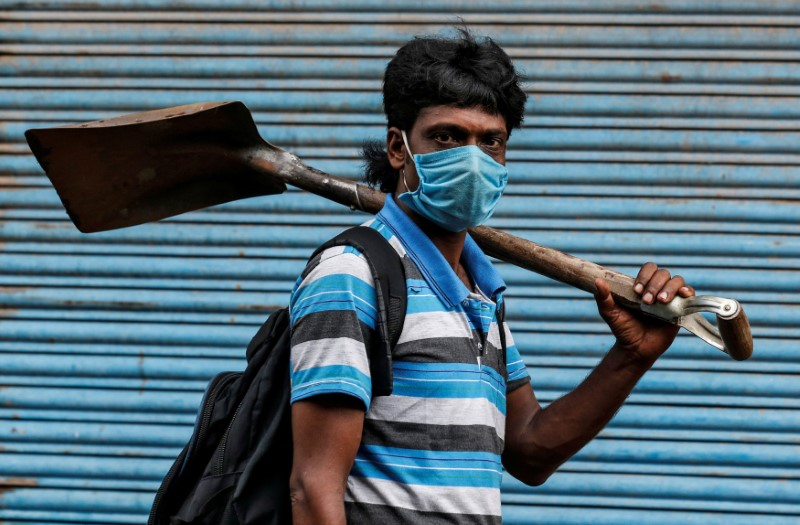 A migrant worker wearing a protective face mask goes to work after few restrictions were lifted, during an extended nationwide lockdown to slow the spread of the coronavirus disease (COVID-19), in Kochi, India, June 1, 2020. REUTERS/Sivaram V - RC250H9ZVHWZ