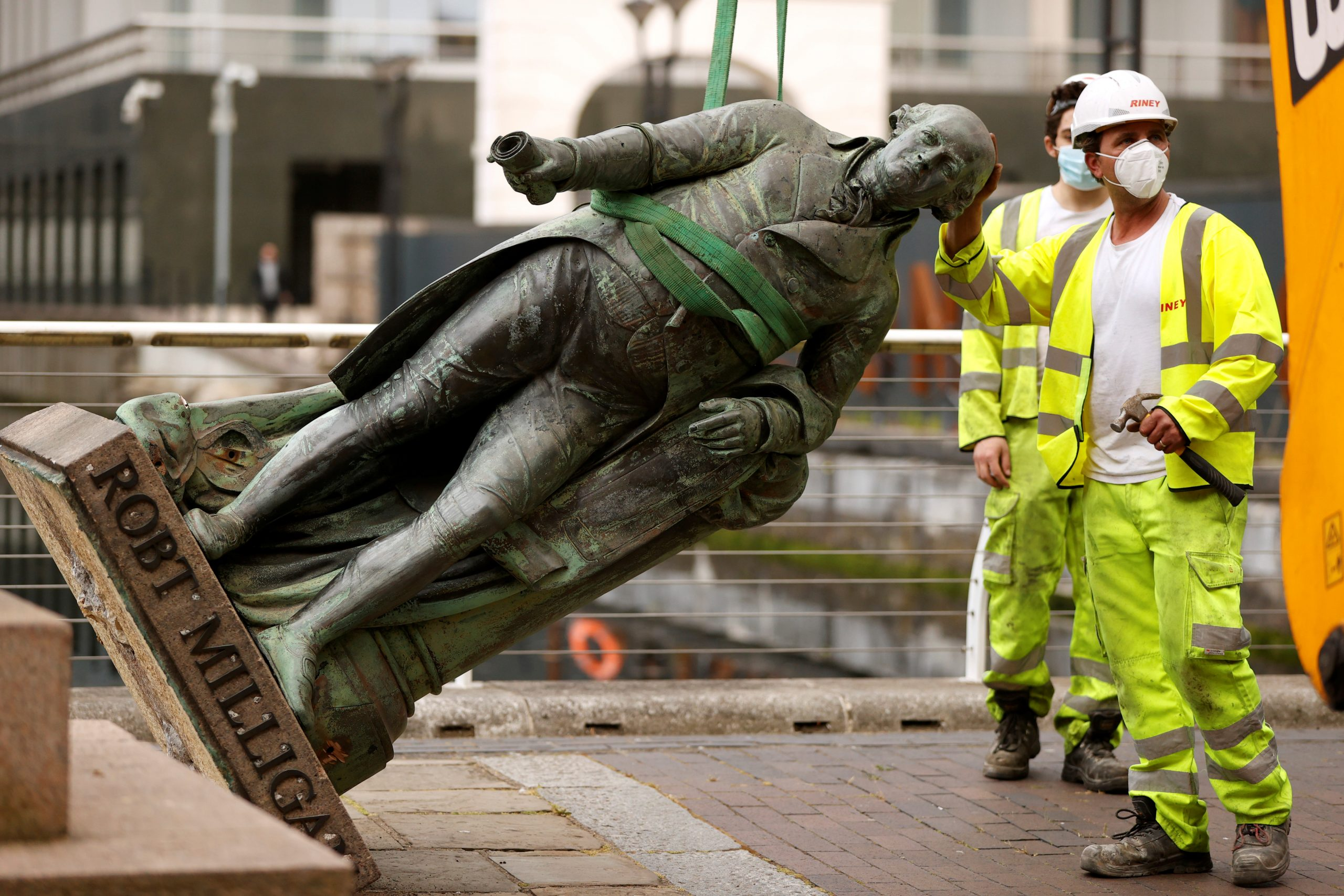 A statue of Robert Milligan is pictured being removed by workers outside the Museum of London Docklands near Canary Wharf, London, on June 9, 2020. (REUTERS/John Sibley)