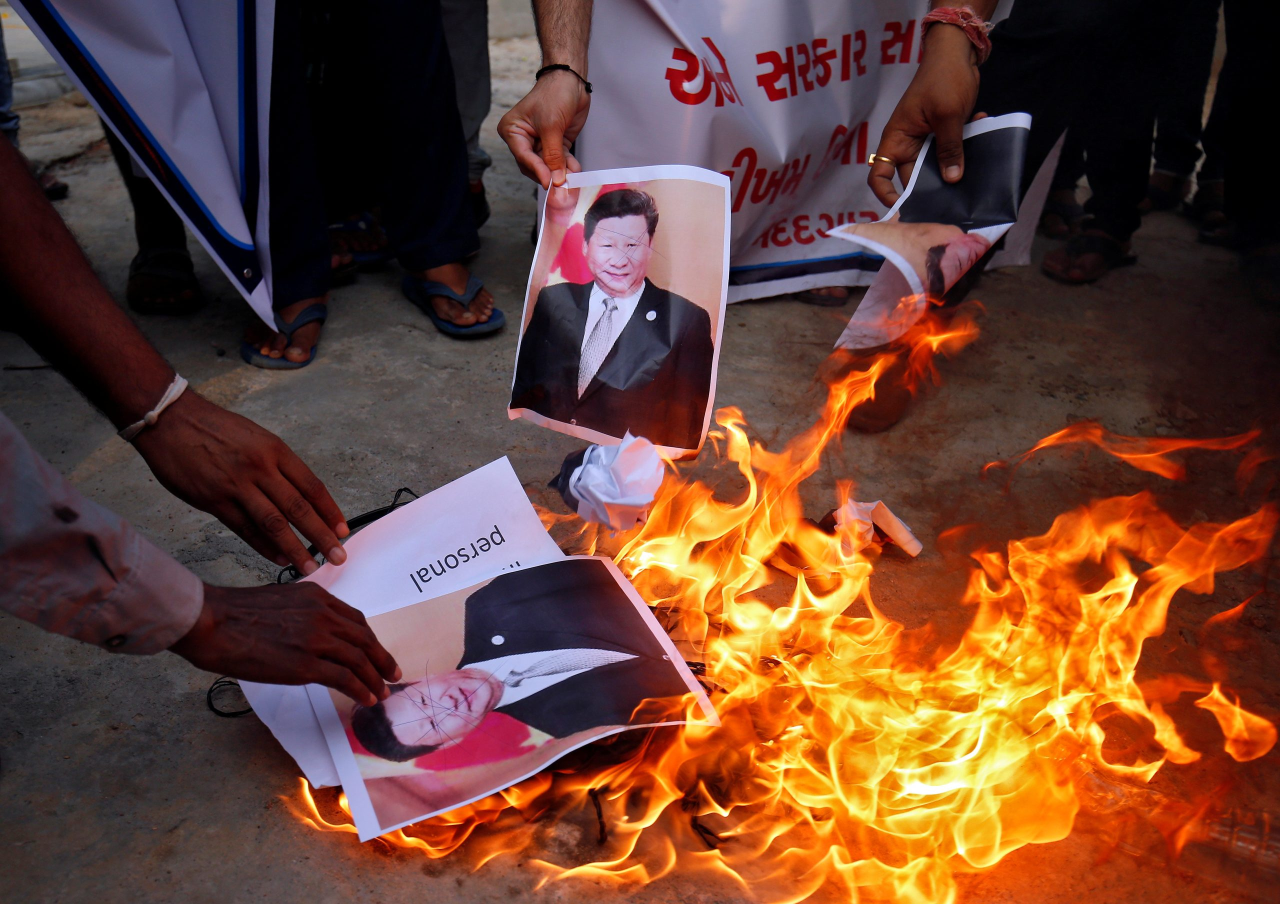 Demonstrators burn posters of Chinese President Xi Jinping during a protest against China, in Ahmedabad, Gujarat. (REUTERS/Amit Dave)