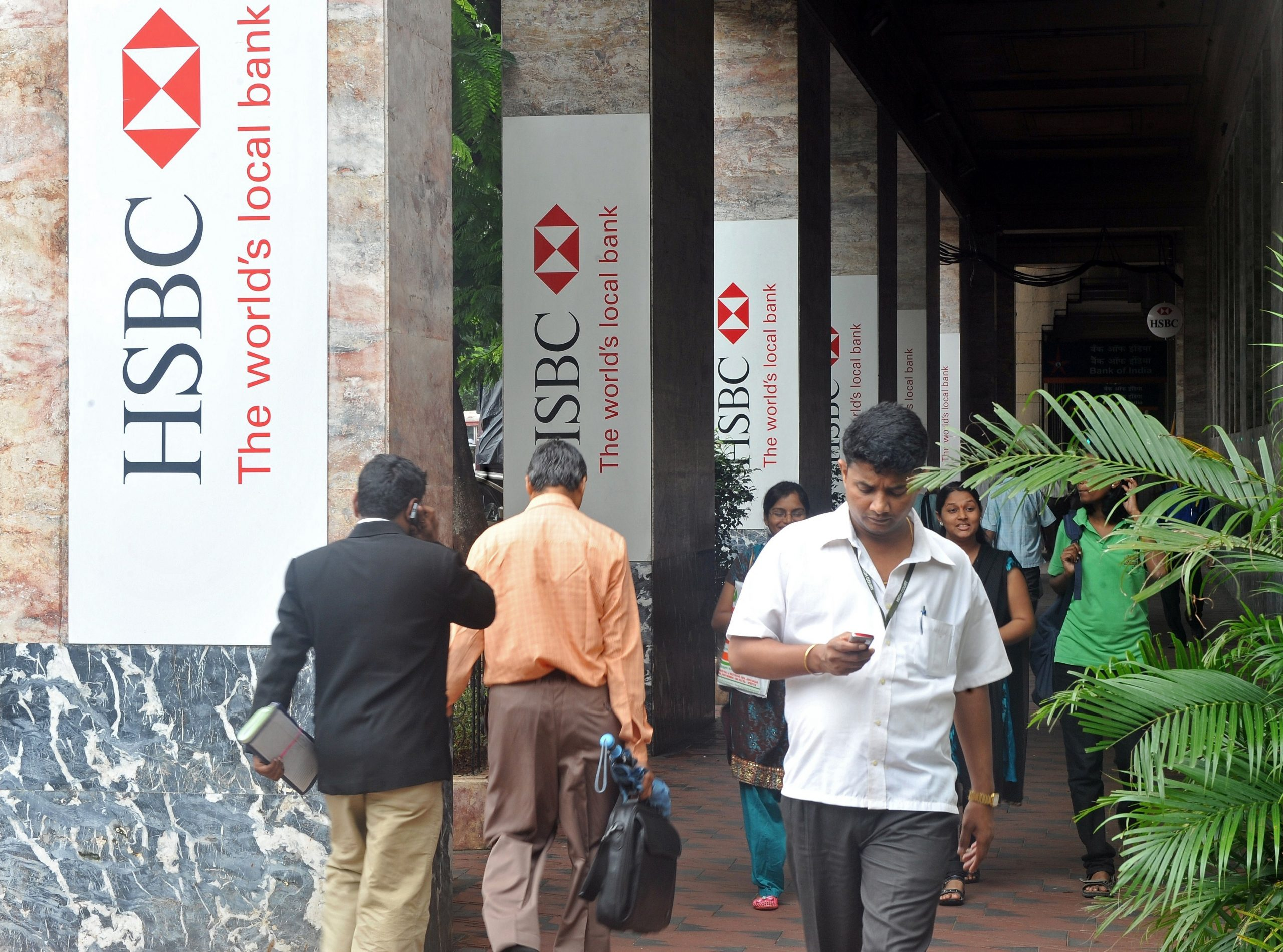 Pedestrians walk past HSBC signage outside the bank's Indian head office in Mumbai on August 2, 2011. Global banking giant HSBC will hire up to 15,000 people in emerging markets over the next three years, a spokeswoman said August 2, a day after it announced plans to slash 30,000 jobs worldwide.  AFP PHOTO/Indranil MUKHERJEE (Photo credit should read INDRANIL MUKHERJEE/AFP via Getty Images)