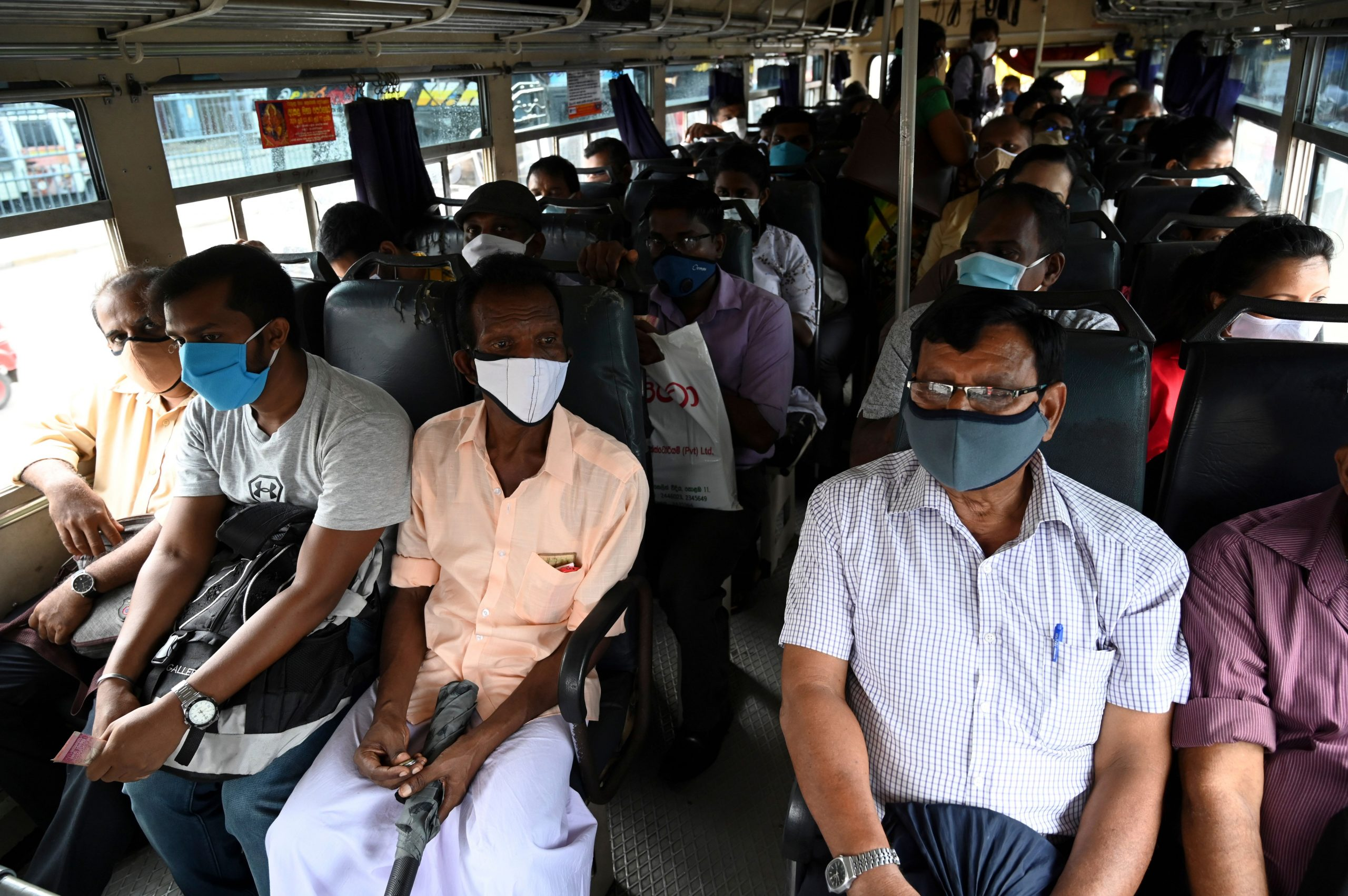 Commuters wearing facemasks travel in a bus in Colombo on May 26, 2020 as authorities eased the 24-hour curfew as a preventive measure against the spread of the COVID-19 coronavirus after 67 days. - The 24-hour curfew first imposed on March 20 was eased on May 26 and turned into a night-time curfew as the authorities announced that the spread of the coronavirus was largely under control. (Photo by Ishara S. KODIKARA / AFP) (Photo by ISHARA S. KODIKARA/AFP via Getty Images)