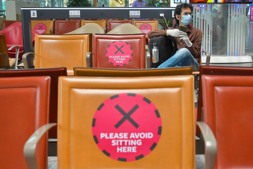 Passengers sit maintaining social distancing at a waiting lounge after check-in at the departure terminal of Bangalore International Airport in Bangalore, on June 2, 2020. (Photo by MANJUNATH KIRAN/AFP via Getty Images)