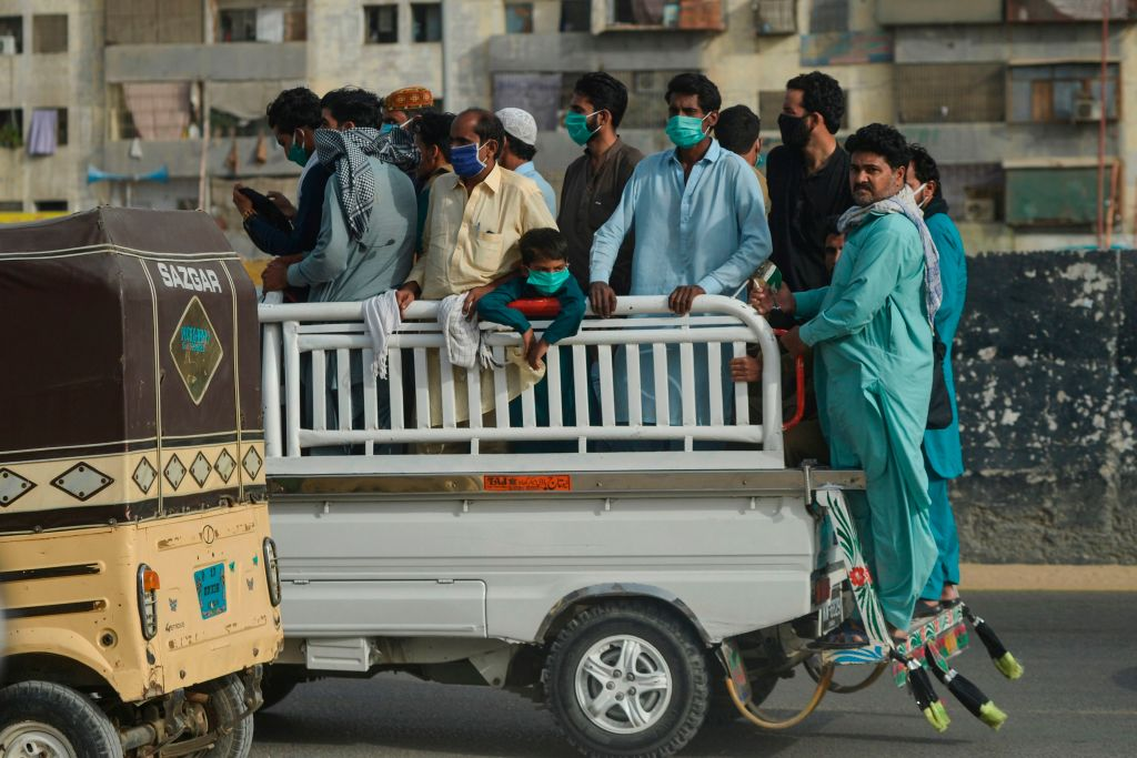 People ride on the back of a vehicle after the government resumed public transport services, in Pakistan's port city of Karachi on June 3, 2020. (Photo by RIZWAN TABASSUM/AFP via Getty Images)