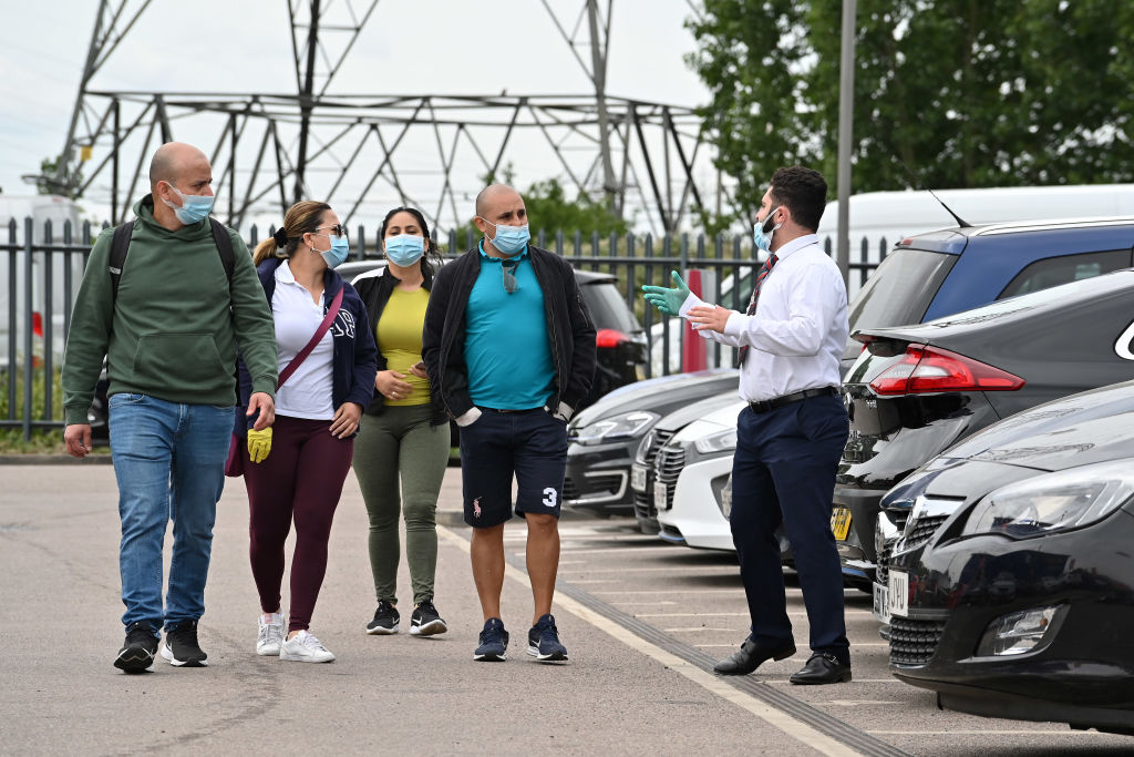 A car salesman (R)  shows customers vehicles at a recently re-opened Vauxhall car dealership in north London on June 4, 2020. (Photo: JUSTIN TALLIS/AFP via Getty Images)