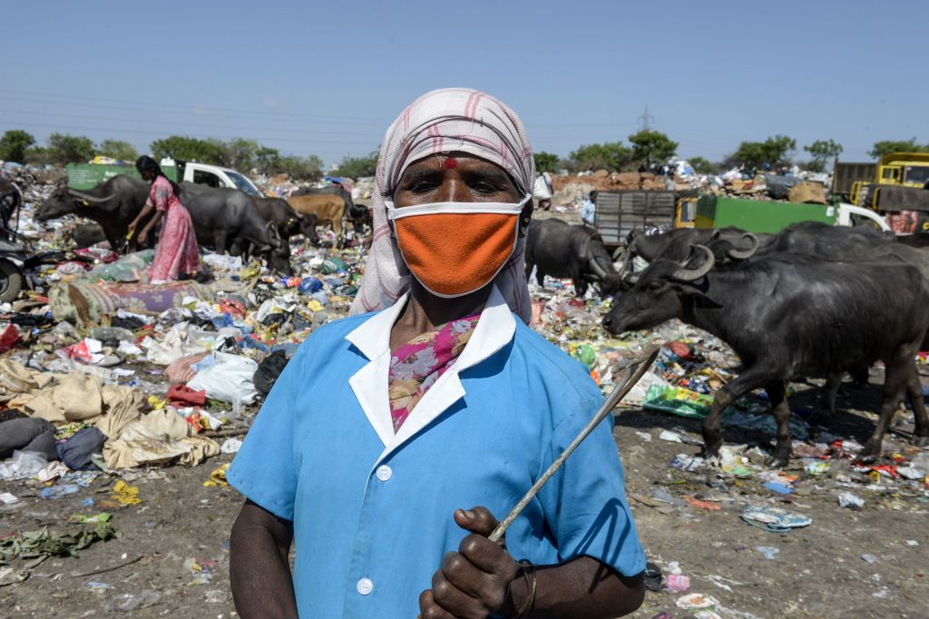 A woman wearing a facemask holds a sickle as she collects recyclable items at a garbage dump site on the outskirts of Hyderabad on the United Nations' World Environment Day on June 5, 2020.(Photo by NOAH SEELAM/AFP via Getty Images)