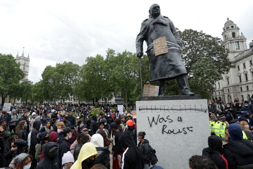 """The statue of former British prime minister Winston Churchill is seen defaced, with the words """"was a racist"""" written under his name on it's base in Parliament Square. (Photo: ISABEL INFANTES/AFP via Getty Images)."""