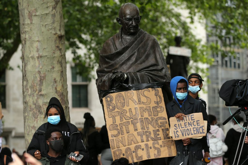 Protesters stand with placards in front of the statue of  Mahatma Gandhi in Parliament Square on June 7, 2020 (Photo: ISABEL INFANTES/AFP via Getty Images).