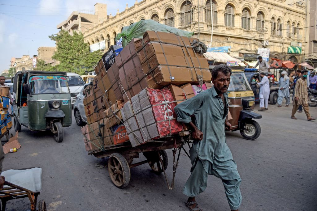 A labourer drags his loaded cart on a street near a market in the Pakistan's port city of Karachi on June 11, 2020. (Photo by RIZWAN TABASSUM/AFP via Getty Images)