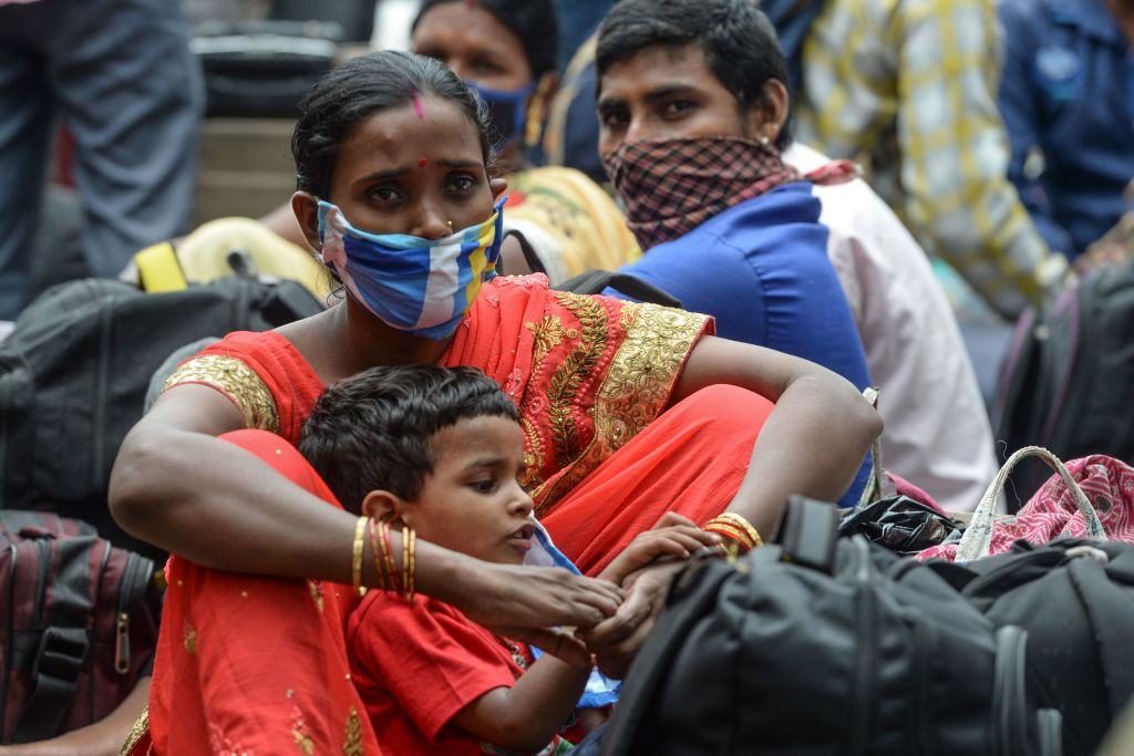 Migrant workers and families wait on the roadside to get transferred to a railway station before boarding special trains to Bihar and Jharkhand states after the government eased a nationwide lockdown imposed as a preventive measure against the COVID-19 coronavirus, in Chennai on June 11, 2020. (Photo by ARUN SANKAR/AFP via Getty Images)