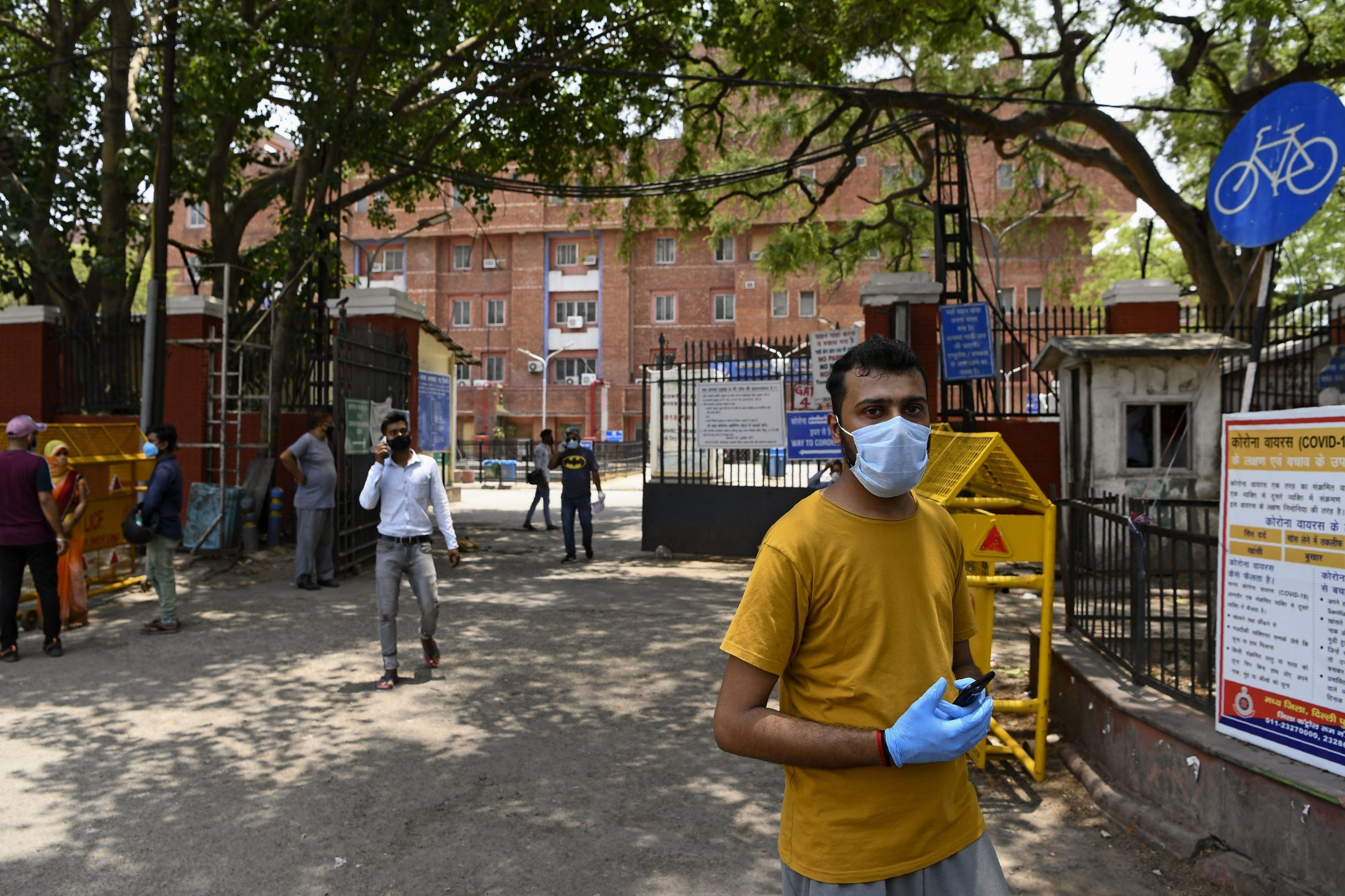 This photo taken on June 11, 2020 shows relatives of a patient suffering from the COVID-19 coronavirus walking out from the entrance of the Lok Nayak Jai Prakash (LNJP) hospital in New Delhi. (Photo by SAJJAD HUSSAIN/AFP via Getty Images)