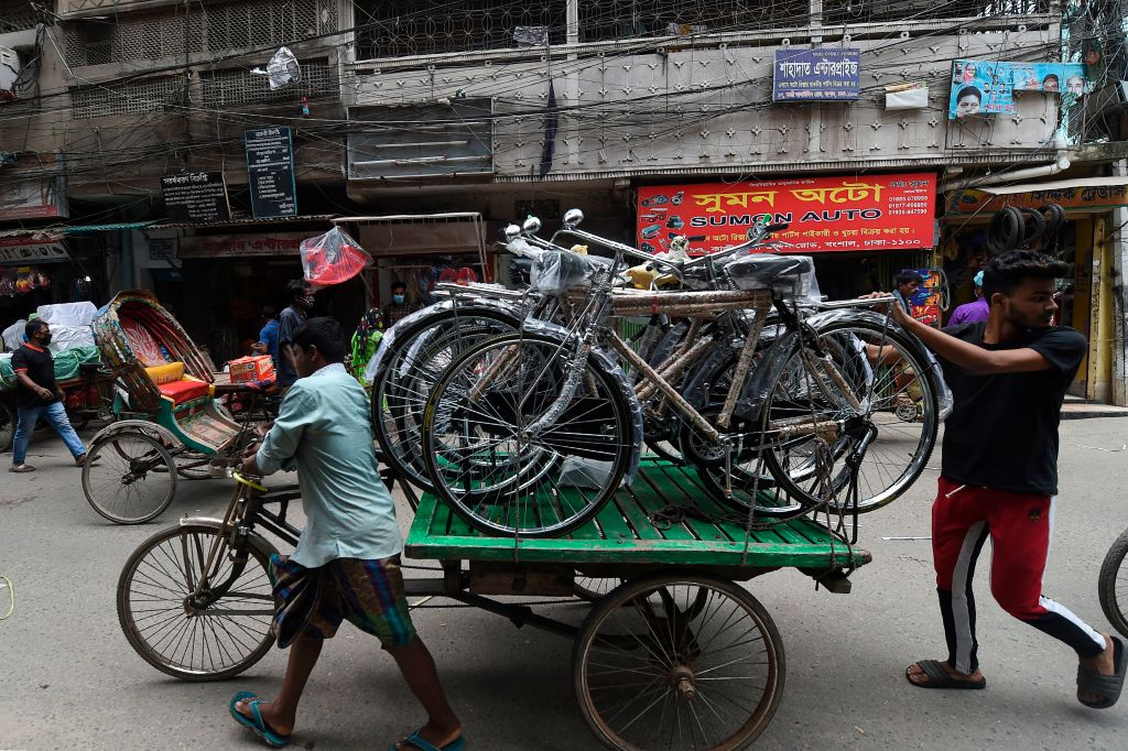 Men pull a cart loaded with bicycles in a bicycle market in Dhaka on June 16, 2020. (Photo by MUNIR UZ ZAMAN/AFP via Getty Images)