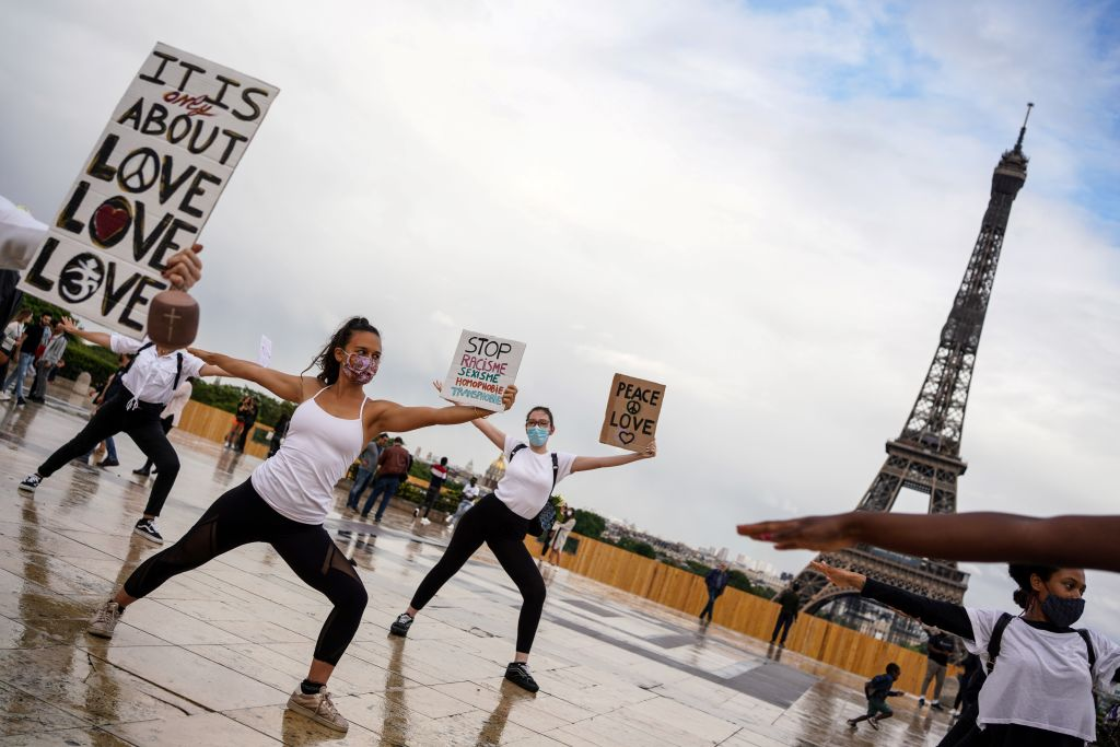 Members of Hermine Prunier's yoga group hold up placards as they perform a choreography to an Indian song for world peace and protest to show their support for the Black Lives Matter movement on the Parvis des droits de l'homme, place du Trocadero, in Paris on June 21, 2020, during the French Festival of Music. (Photo: ABDULMONAM EASSA/AFP via Getty Images)