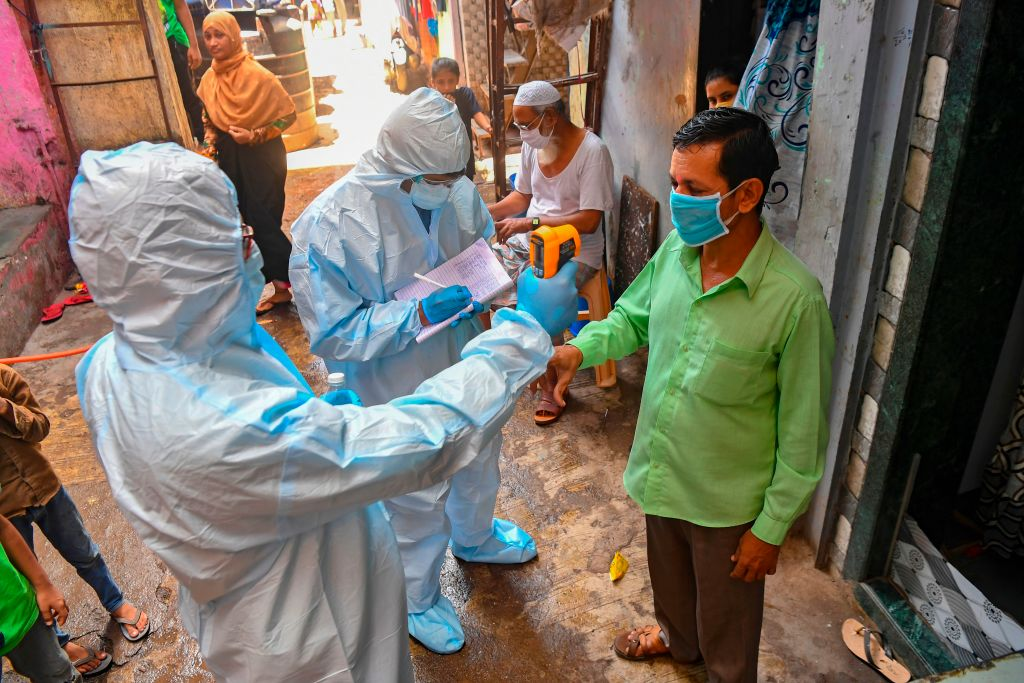 Medical staff wearing Personal Protective Equipment (PPE) gear conduct a door-to-door medical screening inside Dharavi slums to fight against the spread of the COVID-19 coronavirus, in Mumbai on June 24, 2020. (Photo by INDRANIL MUKHERJEE/AFP via Getty Images)
